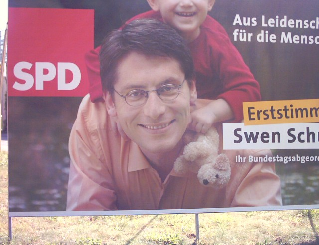an election poster for the Social Democratic Party of Germany (SPD) showing a smiling man with glasses and a boy on his back; the boy is holding a stuffed dog in his left hand
