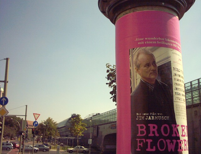 "a movie poster for ""Broken Flowers"" on an advertising column; the poster shows Bill Murray"