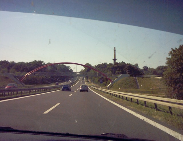 a bridge over a highway seen from inside a car on the highway
