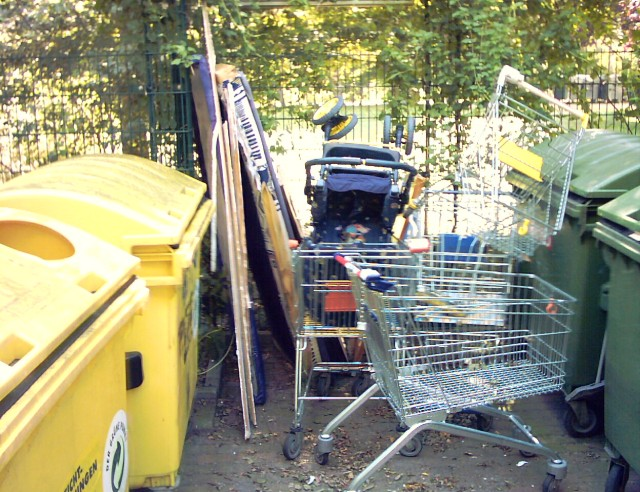 three shopping carts and a baby carriage between waste containers
