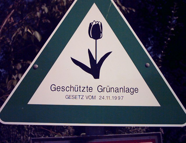 "a triangle-shaped sign with a tulip and the words ""Geschützte Grünanlage"" below"