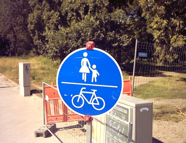 on a blue sign in white a woman with a child in its upper half and a bicycle in its lower half; both halves are separated by a horizontal bar