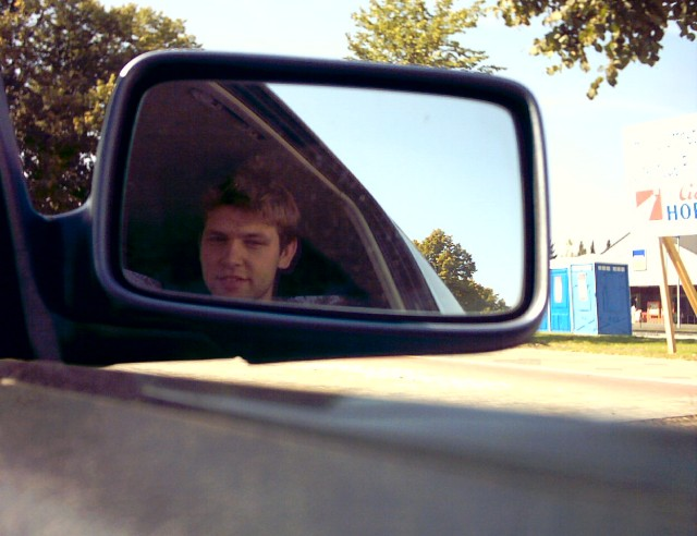 in a car's rear-view mirror a young man's face