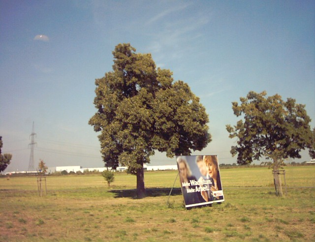 "two trees and an election poster with the words ""Mehr Wachstum. Mehr Arbeit."" on it"