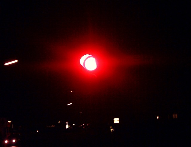 an intensely red traffic light in the dark
