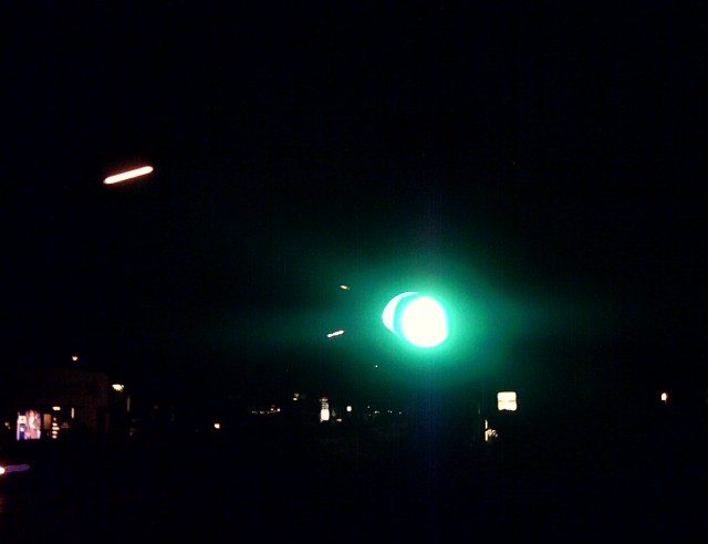 an intensely green traffic light in the dark