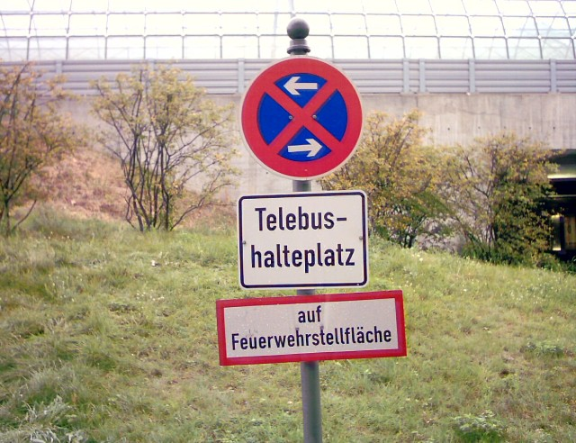 "three signs: the uppermost a stopping restriction sign, below a sign with the word ""Telebushalteplatz"", the lowermost with the words ""auf Feuerwehrstellfläche"""