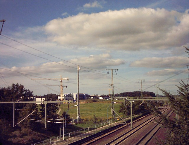 in the foreground four rail tracks next to each other with overhead contact system; in the background a construction site